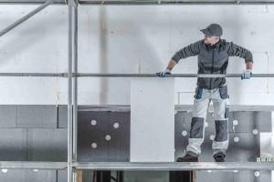 Modern House Insulation. Construction Worker Installing Molded Graphite Polystyrene.
